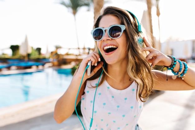 야외 수영장에서 걷고 유행 선글라스에 흥분된 곱슬 무두 질된 여자의 클로즈업 초상화. 무료 사진