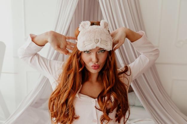 수면 마스크와 긴 물결 모양의 빨간 머리를 가진 종료 재미 있은 여자의 초상화를 닫습니다 침대에서 얼굴을 만든다 무료 사진