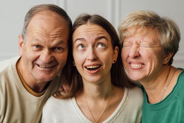 年配の成熟した女性、男性、ミレニアル世代の娘と家族の肖像画を閉じます。 Premium写真