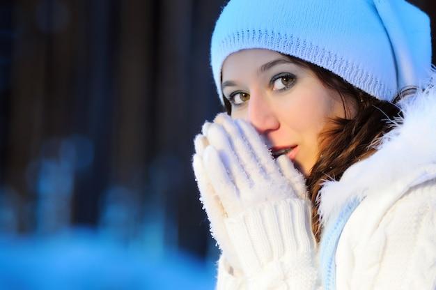 青いニットのスカーフで彼女の顔を覆って、白い冬の帽子と手袋を着用している女の子のクローズアップの肖像画 Premium写真