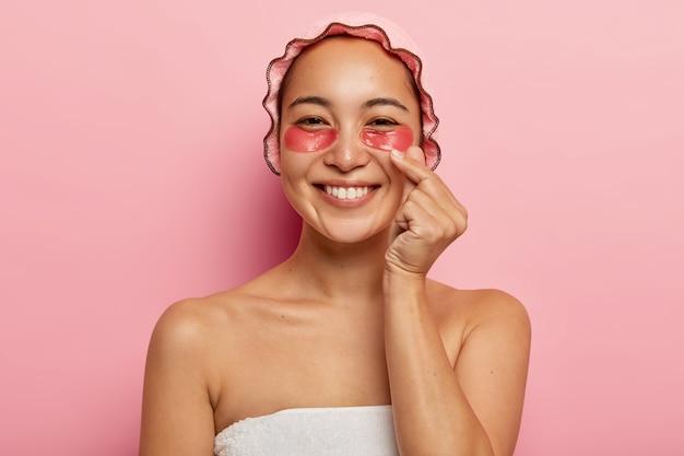 기쁜 한국 여성의 초상화를 닫고, 엄지 손가락과 집게 손가락을 교차하고, 사랑을 보내고, 분홍색 목욕 캡을 착용하고, 눈 밑에 미용 치료를 받고, 보습을 위해 콜라겐 패치를 적용합니다. 무료 사진
