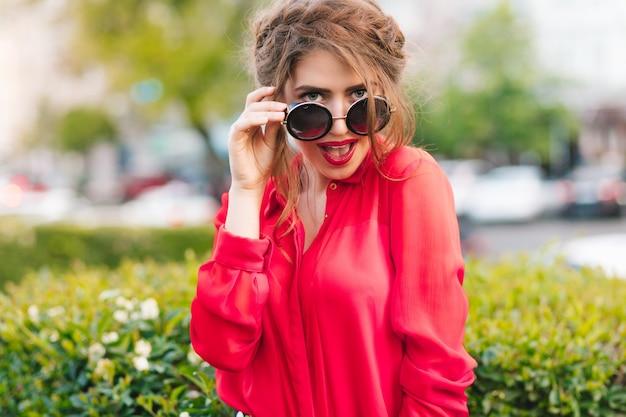 Крупным планом портрет великолепной девушки в солнцезащитных очках, позирует перед камерой в парке. она носит красную блузку и красивую прическу. она смотрит в камеру. Бесплатные Фотографии
