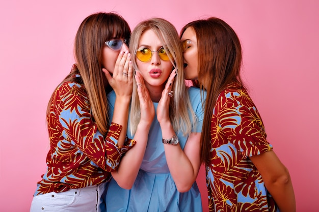 Крупным планом портрет группы забавная стильная женщина, шепчущая секреты друг другу, удивленные возбужденные эмоции, модная цветовая одежда и очки. счастливые друзья веселятся Бесплатные Фотографии
