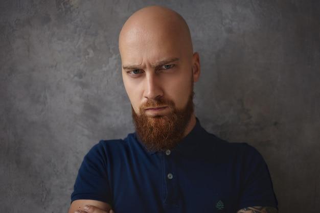 Крупным планом портрет красивого хмурого молодого лысого человека с густой бородой, имеющего сварливый угрюмый взгляд с глазами, полными гнева и ярости. негативные выражения лица и эмоции человека Бесплатные Фотографии
