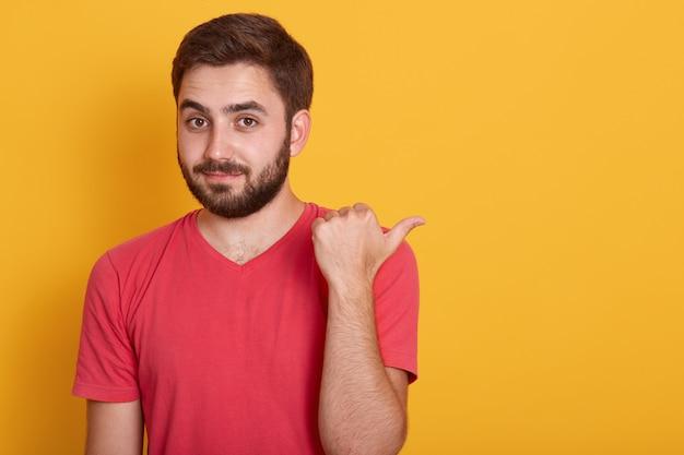 Крупным планом портрет красивый молодой мужчина с бородой, указывая в сторону с большим пальцем Бесплатные Фотографии