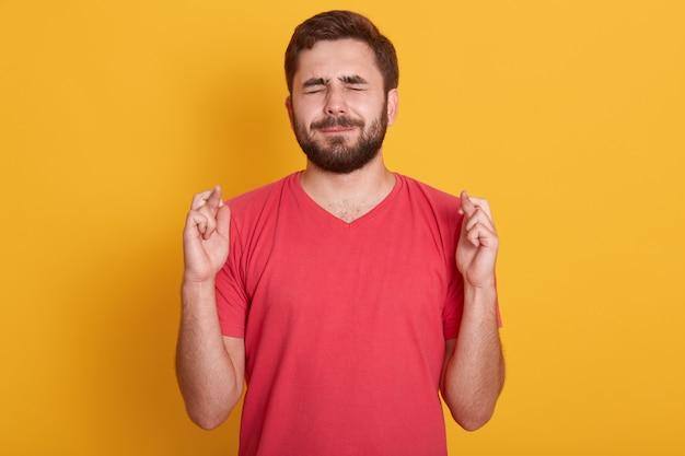 Крупным планом портрет красивого молодого человека в красной футболке с закрытыми глазами и скрещенными пальцами Бесплатные Фотографии