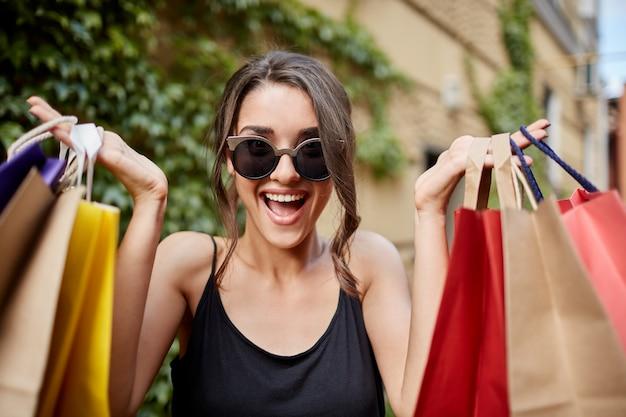 다채로운 쇼핑백을 손에 들고 탭 안경 및 열린 된 입과 행복 식 카메라를 찾고 검은 셔츠에 행복 즐거운 젊은 검은 머리 백인 여자의 초상화를 닫습니다. 미군 병사 무료 사진
