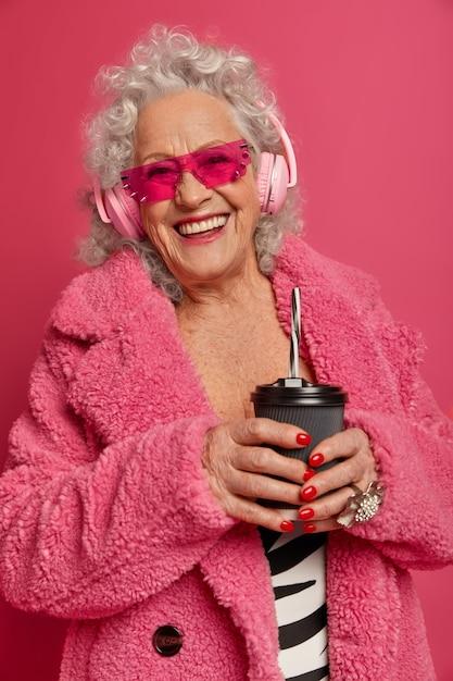 분홍색 스타킹과 코트를 입고 행복한 주름진 유행 할머니의 초상화를 닫습니다 무료 사진