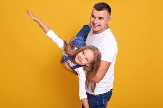 Крупным планом портрет ребенка, играющего с ее папой, девушка на руках отцов, притворяется, летит, разводит руками в стороны Бесплатные Фотографии