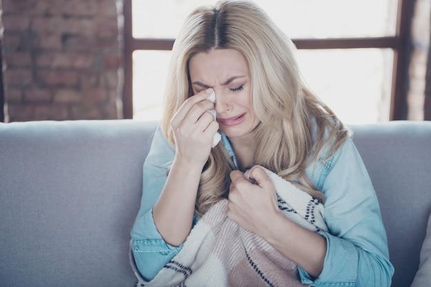 泣いている涙を拭くソファに座っている女性のクローズアップの肖像画 Premium写真