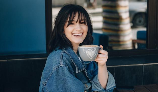 Крупным планом портрет дамы с черными волосами, улыбающейся в камеру и пьющей чашку кофе Premium Фотографии