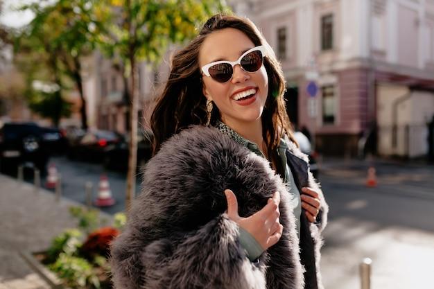 도시 배경에 Laughting 회색 모피 코트에 웃는 갈색 머리 여자의 클로즈업 초상화. 무료 사진