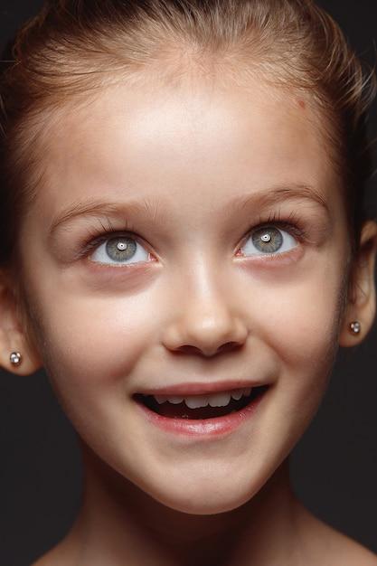 Закройте вверх по портрету маленькой и эмоциональной кавказской девушки. детализированная фотосессия девушки-модели с ухоженной кожей и ярким выражением лица. понятие о человеческих эмоциях. мечтать, смотреть вверх. Бесплатные Фотографии