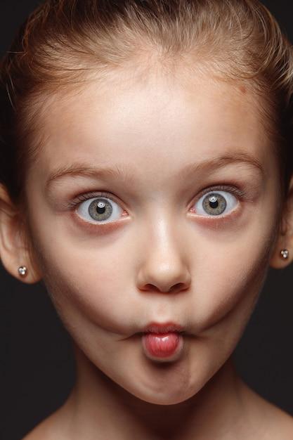 Закройте вверх по портрету маленькой и эмоциональной кавказской девушки. детализированная фотосессия девушки-модели с ухоженной кожей и ярким выражением лица. понятие о человеческих эмоциях. игривые грелки. Бесплатные Фотографии