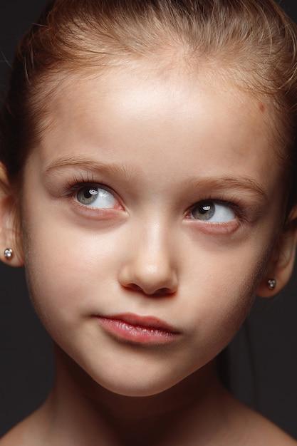 Закройте вверх по портрету маленькой и эмоциональной кавказской девушки. детализированная фотосессия девушки-модели с ухоженной кожей и ярким выражением лица. понятие о человеческих эмоциях. вдумчивый, думающий. Бесплатные Фотографии