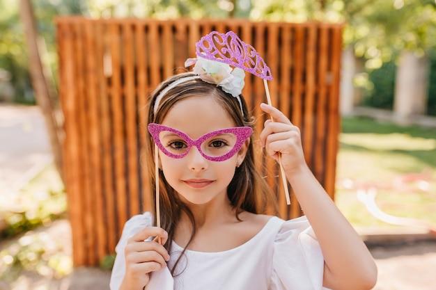 ピンクのメガネと黒髪の白いリボンの小さなファッショナブルな女性のクローズアップの肖像画。おもちゃの輝きの王冠が正面の木製のフェンスでポーズをとっている女の子の屋外写真。 無料写真