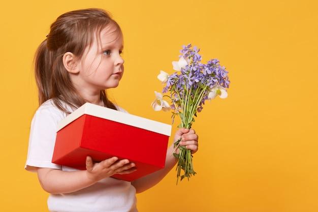 赤いギフトボックスと青い小花の花束を持つ少女の肖像画を閉じる 無料写真