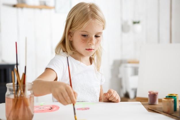 ブロンドの髪と絵を描くことに焦点を当てたそばかすのある白い肌の少女の肖像画を閉じる 無料写真
