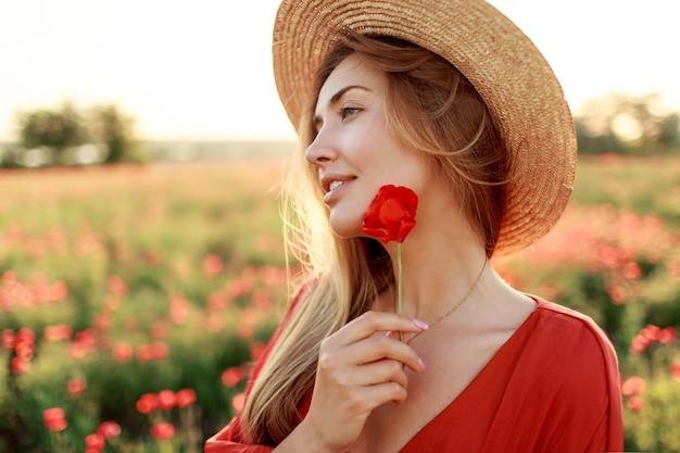 Закройте вверх по портрету милой молодой романтичной женщины с цветком мака в руке, позирующей на фоне поля. в соломенной шляпе. мягкие цвета. Бесплатные Фотографии