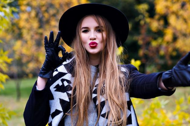秋の写真撮影中に浮気黒の帽子の壮大な女性のクローズアップの肖像画。 9月の日に公園で時間を過ごすエレガントな手袋で面白い若い女性。 無料写真