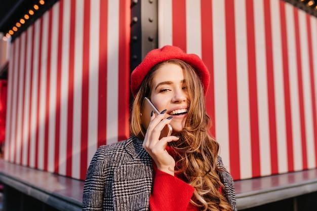 Крупным планом портрет великолепной женщины с блестящими волосами, разговаривающей по телефону на полосатом фоне Бесплатные Фотографии