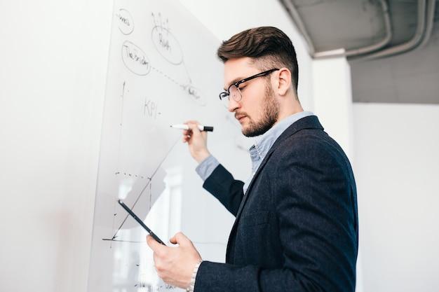 Крупным планом портрет oung темноволосого человека в очках с ноутбуком, написание бизнес-плана на доске. он носит синюю рубашку и темную куртку. вид снизу. Бесплатные Фотографии