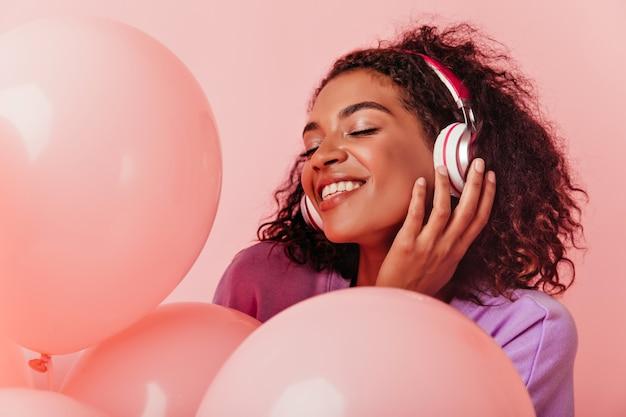 파티를 즐기는 헤드폰에 즐거운 아프리카 여자의 클로즈업 초상화. 생일을 축하하는 동안 기쁜 흑인 여성 듣는 음악. 무료 사진