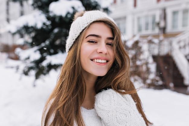 冬の朝を楽しんで誠実な笑顔で満足している金髪の女性のクローズアップの肖像画。屋外の雪景色を見て白い帽子の素敵なヨーロッパの女性。 無料写真