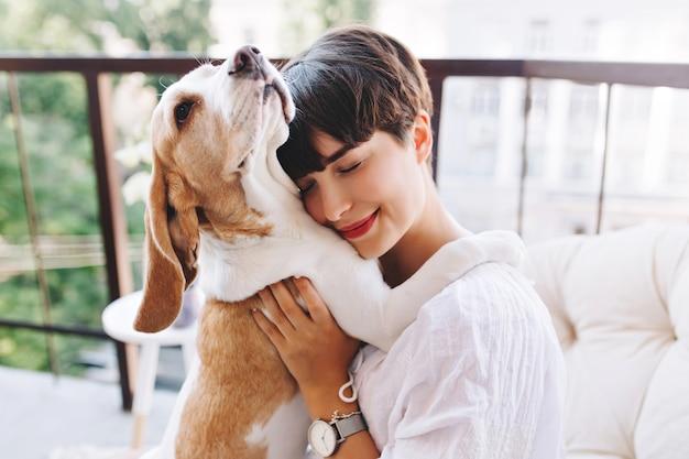目を閉じて面白いビーグル犬を抱きしめる短い茶色の髪の幸せな女の子のクローズアップの肖像画 無料写真