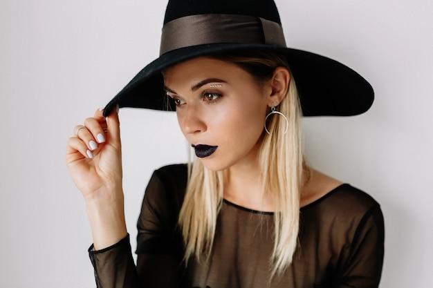격리 된 벽 위에 포즈를 취하는 모자를 쓰고 금발 머리를 가진 꽤 사랑스러운 여자의 초상화를 닫습니다 무료 사진