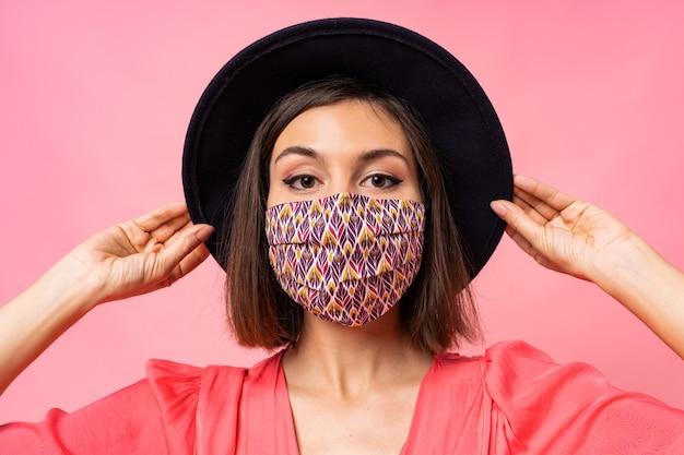 예쁜 여자 옷 보호 세련 된 얼굴 마스크의 초상화를 닫습니다. 검은 모자와 선글라스를 쓰고. 분홍색 벽 위에 포즈 무료 사진