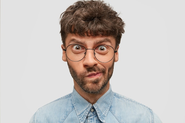 Крупным планом портрет озадаченного бородатого мужчины смотрит в недоумение, поджимает губы, имеет недовольное нервное выражение Бесплатные Фотографии