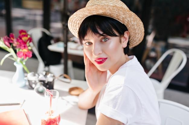 屋外カフェで休んでいる間、光沢のある肌と黒髪のロマンチックな女の子のクローズアップの肖像画 無料写真