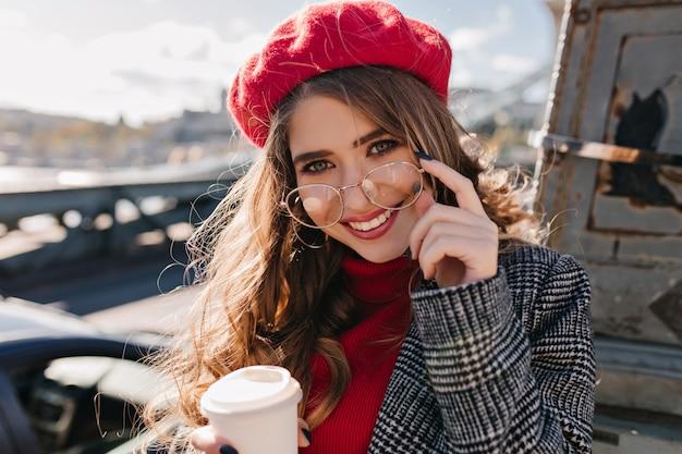 Крупным планом портрет чувственной шатенки с чашкой горячего напитка, позирующей в холодный день Бесплатные Фотографии