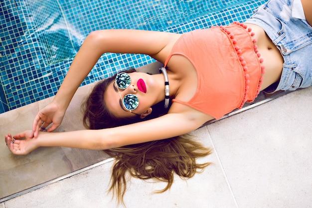 プライベートプールの近くで日光浴をしている官能的なグラマーモデルの肖像画をクローズアップ 無料写真
