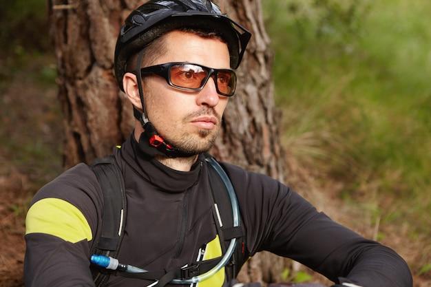 彼の人生について考えて、屋外で木に座って彼の前を見て、サイクリング服、保護用のヘルメット、眼鏡をかけている無精ひげで深刻で思慮深いライダーの肖像画を間近します。 無料写真