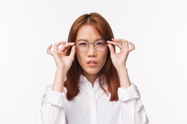 白い壁の上に立って、コンピューターで作業するための眼鏡を選ぶとして視力の世話をして、新しい処方された眼鏡にしようとしている深刻な探している若いアジア女性実業家のクローズアップの肖像画 Premium写真