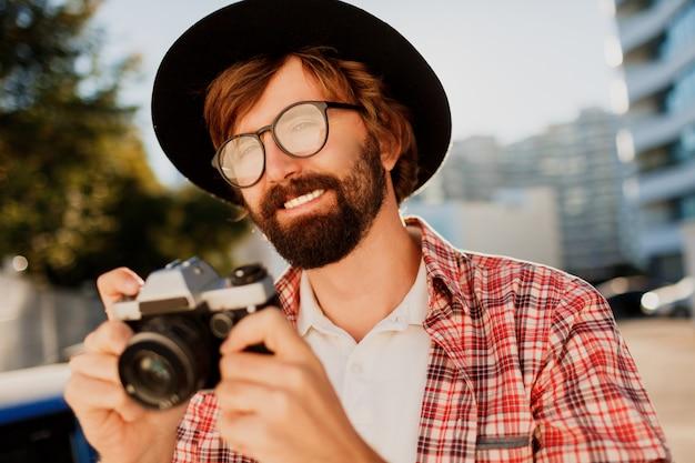 レトロなフィルムカメラを使用して笑顔の流行に敏感なひげ男の肖像画を間近します。 無料写真