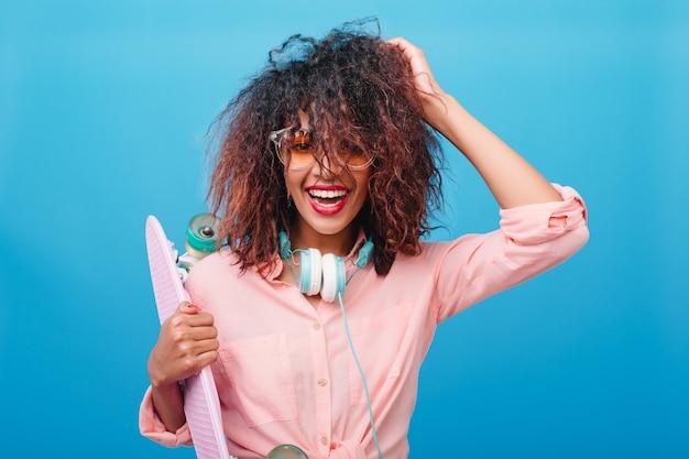 Портрет крупным планом эффектной девушки-мулатки играет с темно-каштановыми волосами на лонгборде. спортивная женщина в наушниках и хлопковой модной рубашке, улыбаясь перед синей стеной. Бесплатные Фотографии