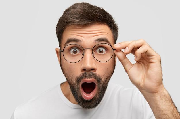 Крупным планом портрет ошеломленного бородатого молодого парня с отвисшей челюстью, приглушенными темными глазами, видит что-то невероятное и удивительное, имеет очки, изолированные на белой стене. люди, концепция эмоций Бесплатные Фотографии