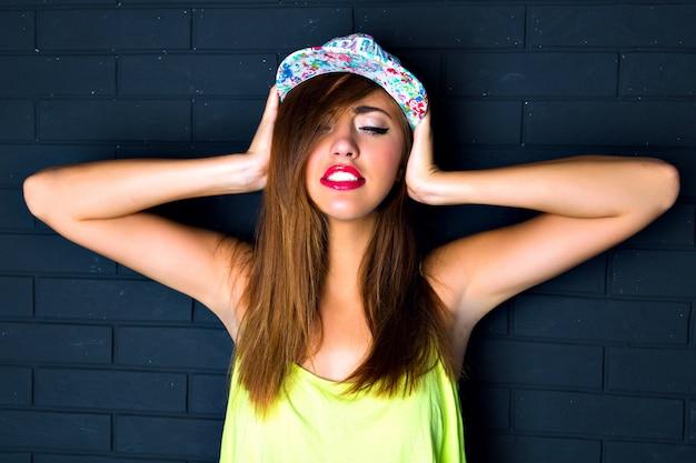 見事なセクシーな女性、明るいアイライナー、完全な光沢のある赤い唇、素晴らしい笑顔、完璧な肌、盗品の帽子、ファッションの肖像画を閉じます。彼女の手を彼女に向けて、目を閉じてください。 無料写真