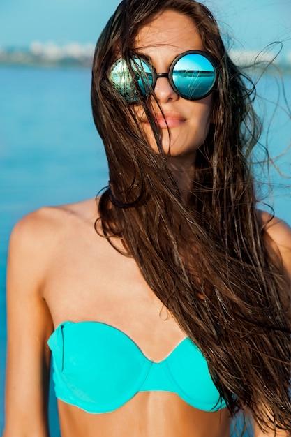 メガネと青い水と太陽が降り注ぐビーチで濡れた髪のスタイリッシュな美しいセクシーな女の子の肖像画を閉じます。日光浴をして、残りをお楽しみください。 無料写真