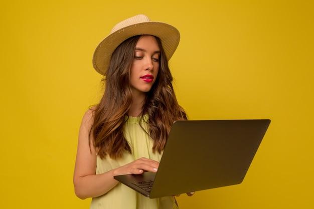 孤立した壁の上のラップトップを使用して長いウェーブのかかった髪の帽子をかぶっているスタイリッシュな女の子のクローズアップの肖像画 無料写真