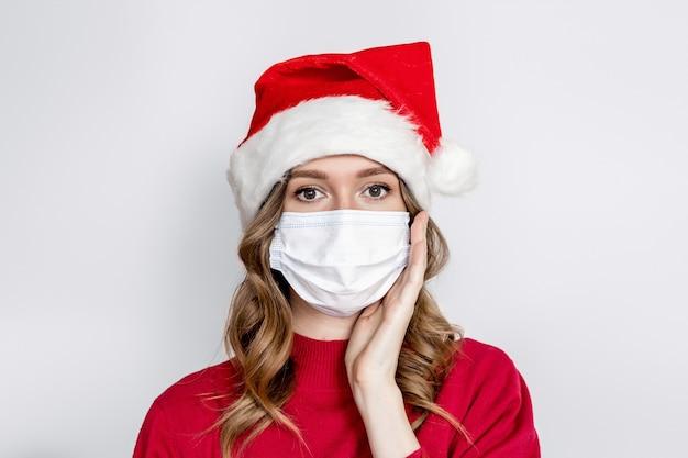 白いスタジオの背景に分離された医療マスクとサンタ帽子を身に着けて手をつないで驚いた白人の女の子の肖像画を閉じます。新年の細菌やウイルスからの保護 Premium写真