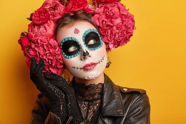 사려 깊은 여자의 초상화를 닫습니다 창의적인 메이크업을 착용하고 미소를 그렸고, 머리 주위에 꽃 화환을 그렸습니다. 무료 사진