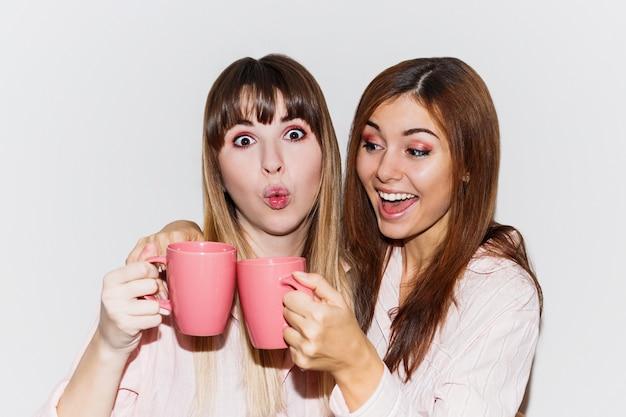 Крупным планом портрет двух веселых белых женщин в розовых пижамах с чашкой чая позирует. портрет со вспышкой. Бесплатные Фотографии
