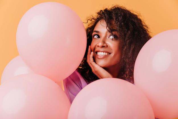 생일 파티에서 재미 사랑스러운 흑인 여성의 클로즈업 초상화. 핑크 풍선과 함께 포즈를 취하는 사랑스러운 아프리카 소녀. 무료 사진