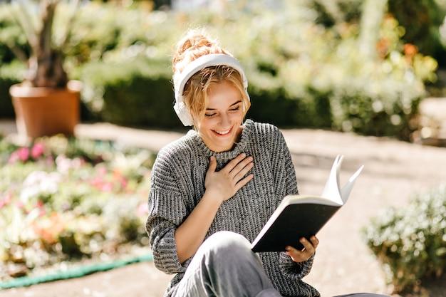 Крупным планом портрет женщины, слушающей музыку и читающей книгу Бесплатные Фотографии