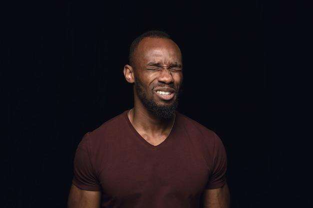 Крупным планом портрет молодого африканского человека на черной студии Бесплатные Фотографии