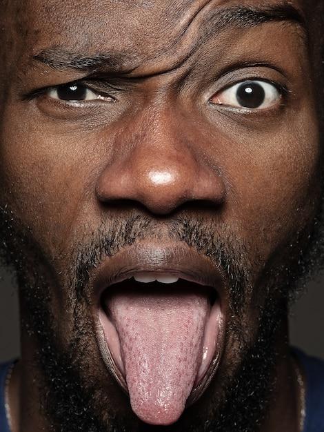 若くて感情的なアフリカ系アメリカ人の男の肖像画をクローズアップ。手入れの行き届いた肌と表情の男性モデルの非常に詳細な写真撮影。人間の感情の概念。舌を垂らして。 無料写真